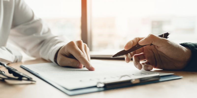Business advisor financial man pointing on contract paper to customer reading contract.