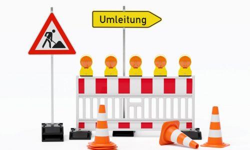 Einzelne Absturzsicherung mit 5 Bakenleuchten gelb-orange, Fußplatten, Schild Baustelle, Schild Umleitung rechtsweisend auf Pfosten steht daneben und Verkehrshütchen Pylone - freigestellt